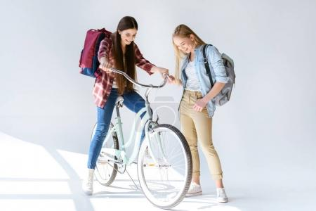 smiling teenagers with bicycle