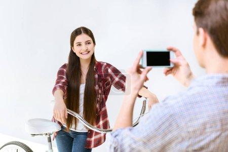 Photo pour Vue arrière du garçon prenant la photo d'une adolescente souriante avec vélo sur smartphone isolé sur blanc - image libre de droit