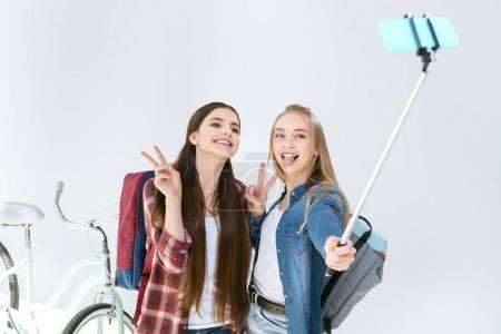 Photo for Teenage friends showing peace sign while taking selfie together isolated on white - Royalty Free Image