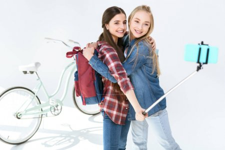 Photo for Happy teenagers hugging each other while taking selfie together on white - Royalty Free Image