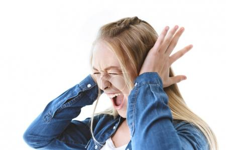 Photo for Side view of screaming teenage girl covering ears isolated on white - Royalty Free Image