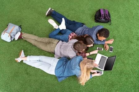 multiethnic teenagers with laptop on green lawn