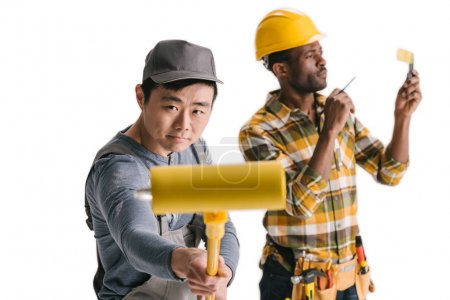 African-american and asian construction workers with tools