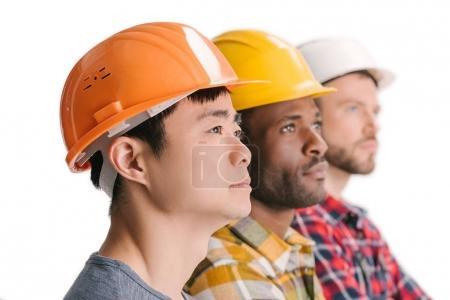 Photo pour Vue de côté du groupe de travailleurs de la construction réfléchis et multiethniques en rangée - image libre de droit