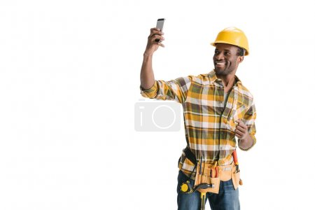 Photo for Smiling african-american builder taking selfie isolated on white - Royalty Free Image