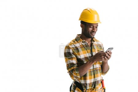 Photo for Smiling african-american builder texting messege on smartphone isolated on white - Royalty Free Image