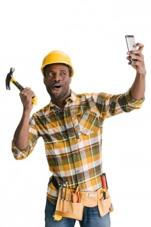 Photo for Funny african-american builder taking selfie isolated on white - Royalty Free Image