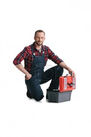Photo for Smiling handsome construction worker with toolbox isolated on white - Royalty Free Image