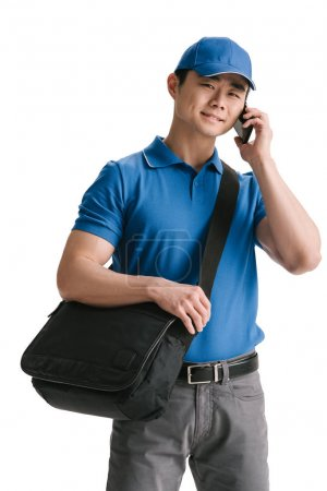 young asian courier talking smartphone