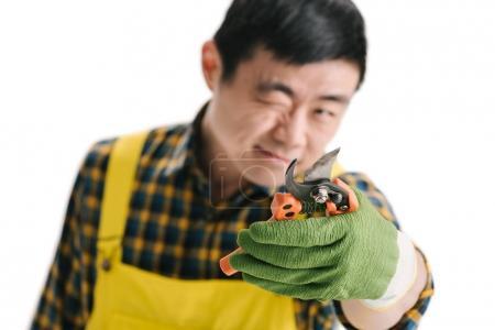 handsome asian gardener with secateurs