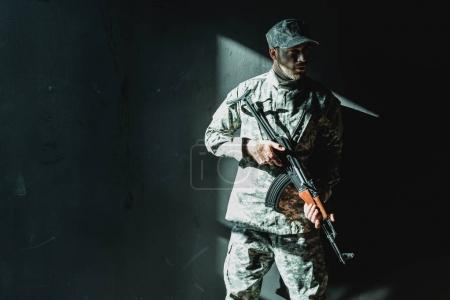 Soldier in military uniform with rifle leaning bac...