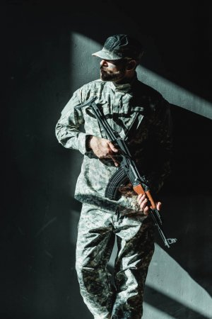 Photo pour Soldat en uniforme militaire avec fusil appuyé sur mur en béton - image libre de droit