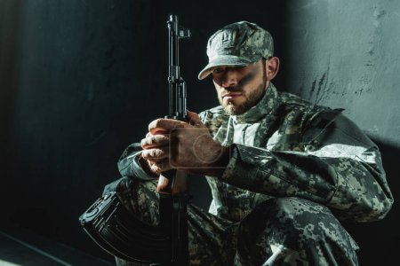 Photo for Focused soldier in military uniform with rifle next to concrete wall - Royalty Free Image