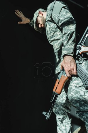 Photo for Mourning soldier with rifle leaning on wall isolated on black - Royalty Free Image