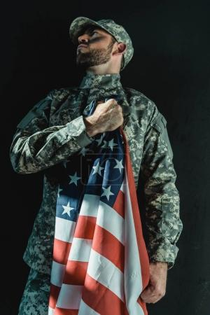 Photo for Soldier holding united states flag on heart isolated on black - Royalty Free Image