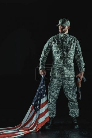 Photo for Soldier with united states flag and rifle isolated in black - Royalty Free Image
