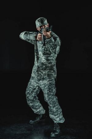 Photo pour Soldat en uniforme militaire avec fusil visant isolée sur fond noir - image libre de droit