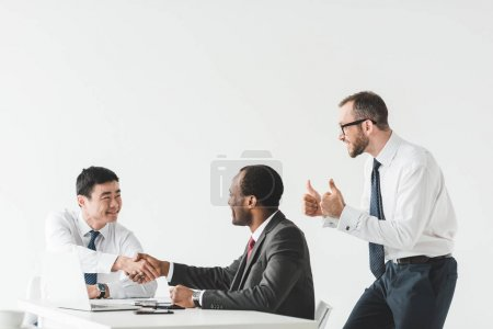 Photo for Multiethnic businessmen shaking hands during meeting with colleague showing thumbs up near by isolated on white - Royalty Free Image