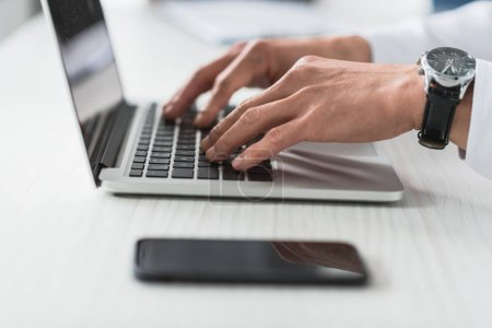 Photo for Cropped shot of businessman typing on laptop at workplace - Royalty Free Image