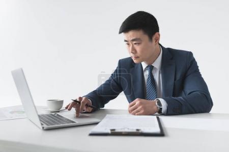 Photo pour Concentré homme d'affaires asiatique en costume travaillant sur ordinateur portable au lieu de travail - image libre de droit