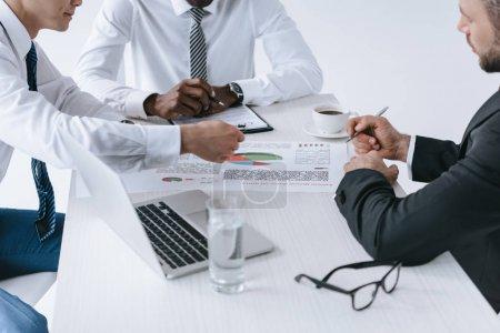 Photo pour Vue partielle des hommes d'affaires multiethniques discutant nouveau projet sur lieu de travail - image libre de droit