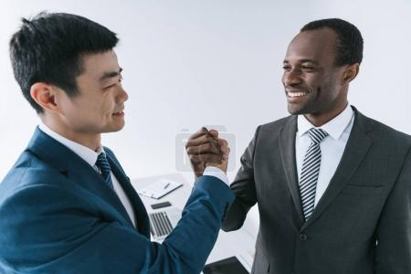 Photo for Smiling african american and asian businessmen shaking hands after meeting - Royalty Free Image