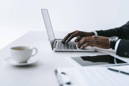 Photo pour Vue partielle de l'homme d'affaires afro-américain tapant sur ordinateur portable sur le lieu de travail isolé sur blanc - image libre de droit