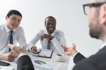 Photo pour Hommes d'affaires multiethniques en discussion lors d'une réunion sur le lieu de travail - image libre de droit
