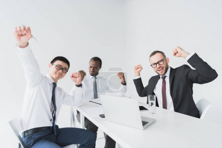 multicultural excited businessmen at workplace
