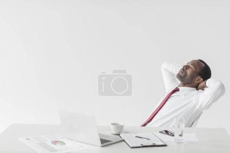Photo pour Portrait d'un homme d'affaires afro-américain reposant sur un espace de travail avec des documents et un ordinateur portable isolé sur du blanc - image libre de droit