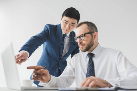 Photo for Portrait of multiethnic focused businessmen working on laptop together at workplace isolated on white - Royalty Free Image