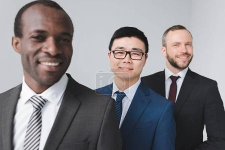 Photo for Portrait of multiethnic smiling businessmen in suits looking at camera isolated on grey - Royalty Free Image