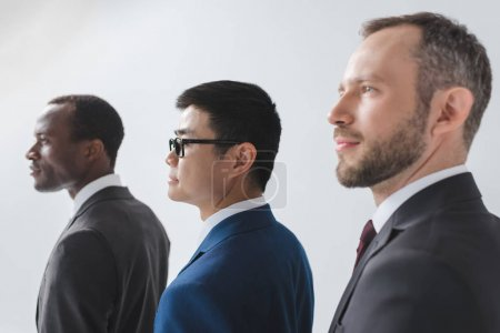 Photo for Side view of multiethnic group of businessmen in suits isolated on grey - Royalty Free Image