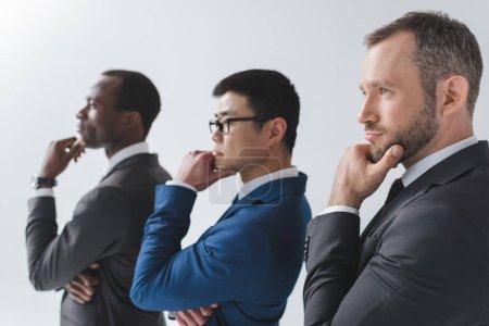 Photo pour Vue du côté de multiethniques entrepreneurs pensifs regardant loin isolé sur fond gris - image libre de droit