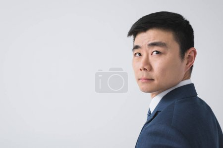 Photo for Portrait of thoughtful asian businessman looking away isolated on grey - Royalty Free Image