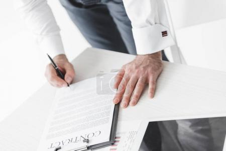 Photo pour Vue partielle de l'entrepreneur, signature du contrat au lieu de travail - image libre de droit