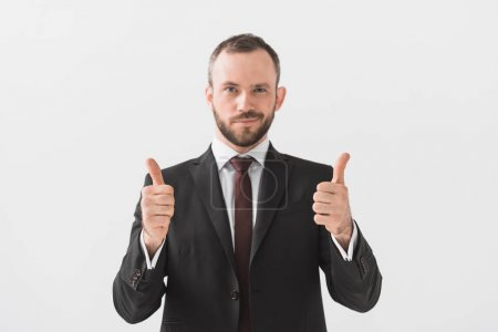 Photo for Portrait of businessman showing thumbs up and looking at camera isolated on white - Royalty Free Image