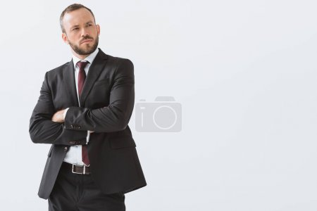 Photo for Portrait of stylish businessman in suit with arms crossed looking away isolated on white - Royalty Free Image