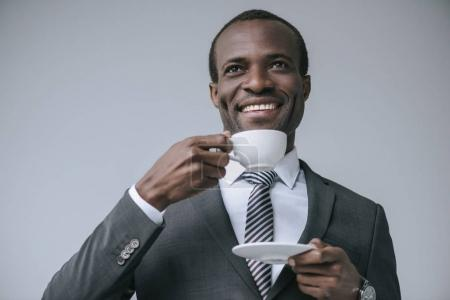 Photo for Portrait of cheerful african american businessman drinking coffee isolated on grey - Royalty Free Image