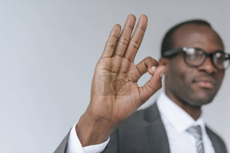 Photo for Selective focus african american businessman in eyeglasses showing ok sign isolated on grey - Royalty Free Image