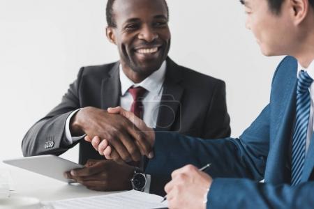 Foto de Sonrientes afroamericanos y asiáticos hombres de negocios estrechando la mano después de conocer - Imagen libre de derechos