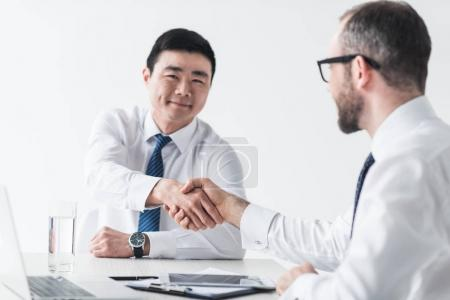 Photo for Multicultural businessmen shaking hands at workplace on meeting isolated on white - Royalty Free Image
