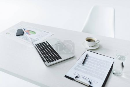 Photo for Selective focus of laptop, cup of coffee and contract at workplace isolated on white - Royalty Free Image