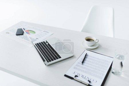 Photo pour Foyer sélectif de l'ordinateur portable, tasse de café et contrat sur le lieu de travail isolé sur blanc - image libre de droit