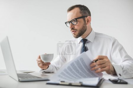 Photo for Portrait of focused businessman with cup of coffee doing paperwork at workplace - Royalty Free Image