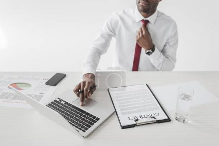 Photo for African american businessman sitting at workplace with documents and working on laptop isolated on grey - Royalty Free Image