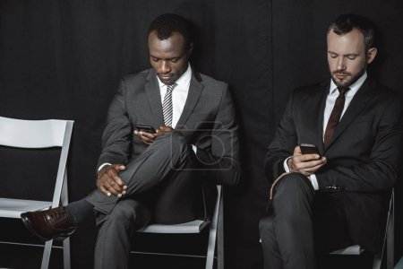 Photo for Multicultural businessmen in suits using smartphones while waiting for job interview - Royalty Free Image