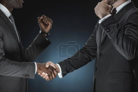 Photo for Cropped shot of multicultural businessmen handshake isolated on black - Royalty Free Image