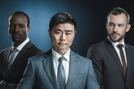 Photo for Selective focus of multicultural group of businessmen in suits looking at asian colleague isolated on black - Royalty Free Image