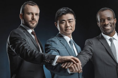Photo for Portrait of multiethnic businessmen looking at camera while holding hands together isolated on black - Royalty Free Image